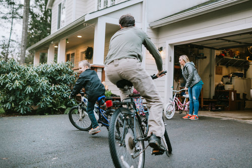 Family Riding Bikes in Home Asphalt Driveway